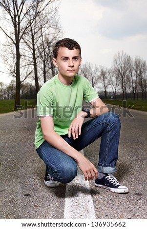 Full length portrait of a young boy posing outdoors