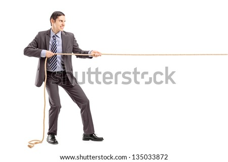 Full length portrait of a young businessman in suit pulling a rope isolated on white background - stock photo