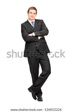 Full length portrait of a young businessman leaning against wall isolated on white background - stock photo