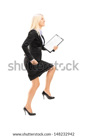 Full length portrait of a young businesswoman doing a huge step towards isolated on white background - stock photo