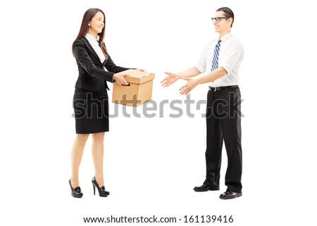 Full length portrait of a young businesswoman giving a box to her colleague, isolated on white background - stock photo