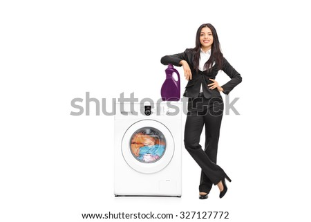Full length portrait of a young businesswoman standing by a washing machine and leaning on a laundry detergent isolated on white background - stock photo
