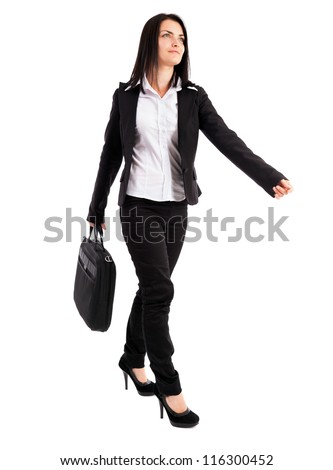 Full length portrait of a young businesswoman walking while holding a bag isolated on white background