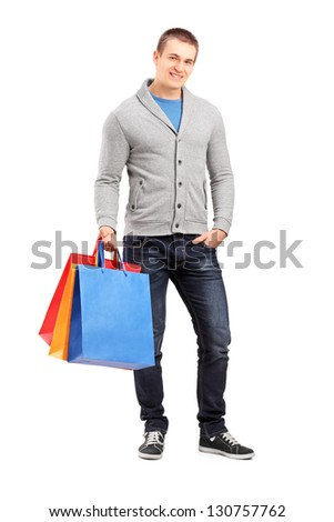 Full length portrait of a young casual man holding shopping bags isolated against white background - stock photo