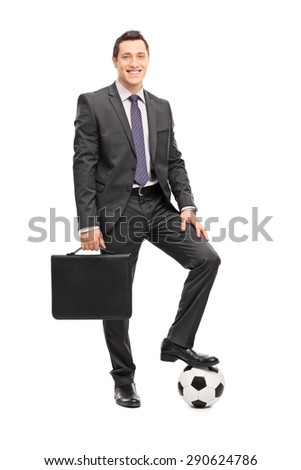 Full length portrait of a young cheerful businessman in a black suit holding a suitcase and posing with a football under his foot isolated on white background - stock photo