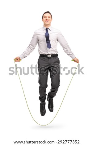 Full length portrait of a young cheerful businessman jumping a rope and looking at the camera isolated on white background - stock photo