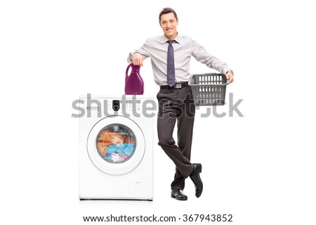 Full length portrait of a young cheerful businessman standing next to a washing machine isolated on white background - stock photo