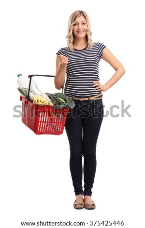 Full length portrait of a young cheerful woman carrying a shopping basket full of groceries isolated on white background - stock photo