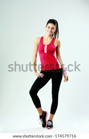 Full-length portrait of a young cheerful woman standing on gray background - stock photo