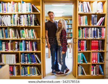 Full length portrait of a young couple by bookshelves in the library - stock photo