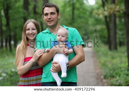 Full length portrait of a young couple in love, parents posing in the summer park - stock photo
