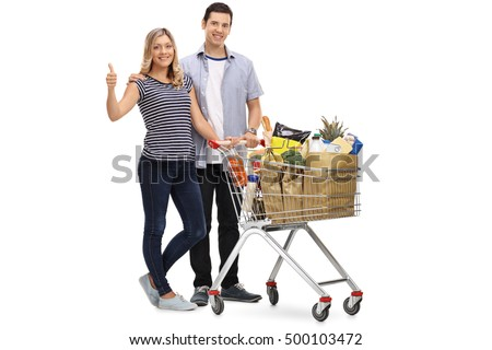 Full length portrait of a young couple posing with a shopping cart full of groceries and giving a thumb up isolated on white background