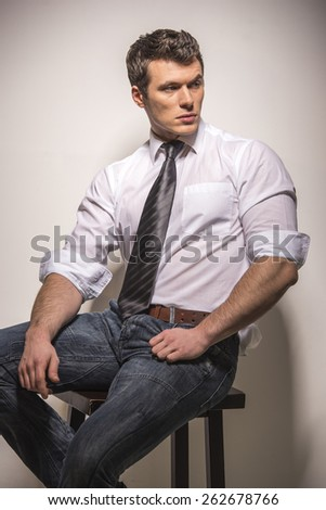 Full length portrait of a young fashion man is sitting on a chair and is looking towards on a light background.