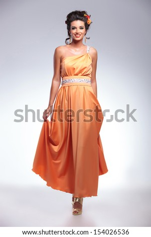 full length portrait of a young fashion woman walking toward the camera with a smile on her face. on gray background