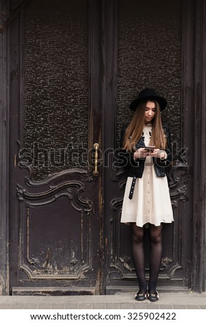 Full length portrait of a young fashionable hipster girl with long brunette hair chatting on her cell telephone, stylish woman with trendy look using mobile phone while standing against vintage door  - stock photo
