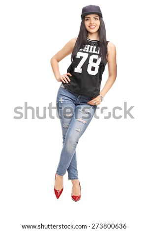 Full length portrait of a young fashionable woman in hip-hop outfit, leaning against a wall isolated on white background - stock photo