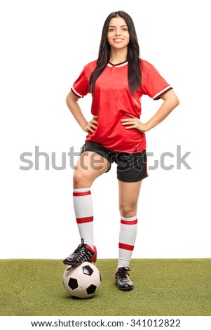 Full length portrait of a young female football player stepping over a ball on a grass field and looking at the camera isolated on white background - stock photo
