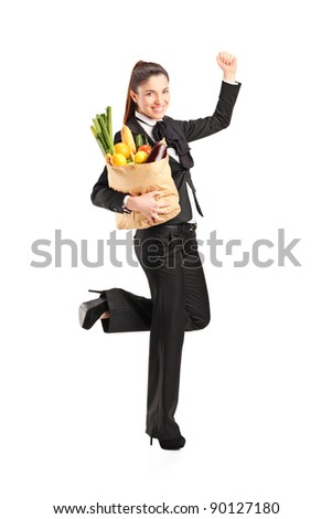Full length portrait of a young female holding a paper bag with groceries isolated on white background - stock photo