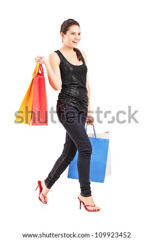 Full length portrait of a young female holding shopping bags and walking, isolated on white background