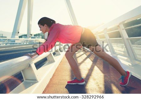 Full length portrait of a young female jogger stretches legs muscles before a fitness training on the fresh air outside, attractive woman runner dressed in sportswear working out outdoors in evening - stock photo