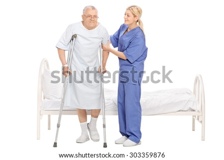 Full length portrait of a young female nurse helping a senior patient with crutches isolated on white background - stock photo