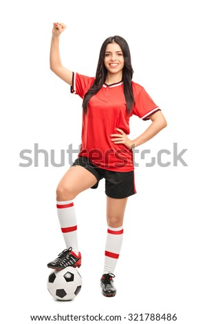 Full length portrait of a young female soccer player stepping over a ball and gesturing happiness isolated on white background - stock photo