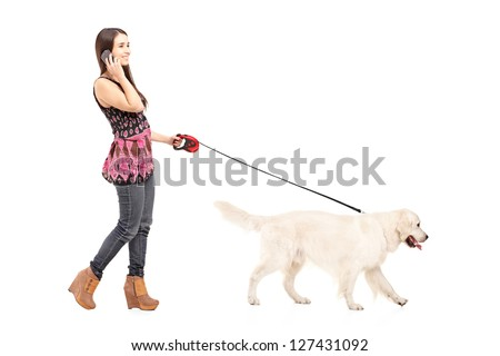 Full length portrait of a young female walking her dog and talking on a mobile phone isolated on white background