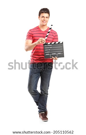 Full length portrait of a young filmmaker holding a movie-clapper isolated on white background