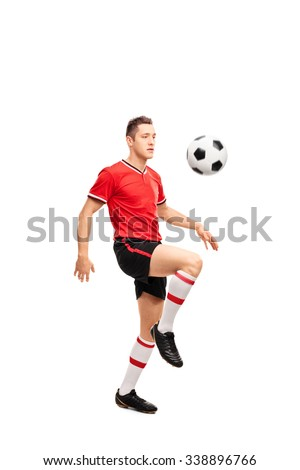 Full length portrait of a young football player juggling a ball on his knees isolated on white background - stock photo