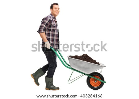 Full length portrait of a young gardener pushing a wheelbarrow full of dirt isolated on white background - stock photo