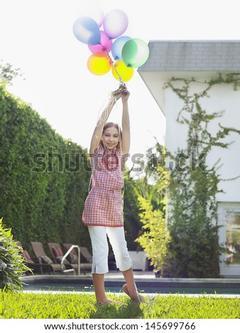 Full length portrait of a young girl holding bunch of balloons over head in lawn - stock photo