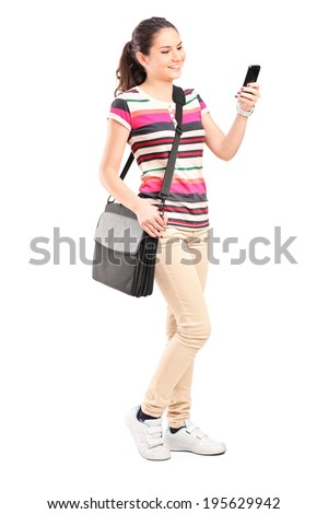 Full length portrait of a young girl looking at a cell phone isolated on white background