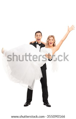 Full length portrait of a young groom lifting his bride in his hands isolated on white background