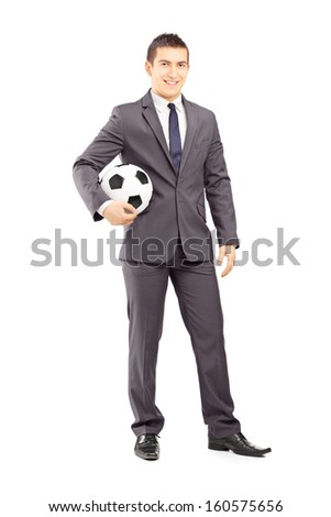 Full length portrait of a young handsome businessman holding a football isolated on white background - stock photo