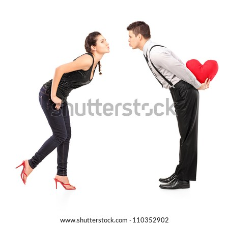 Full length portrait of a young heterosexual couple about to kiss isolated on white background