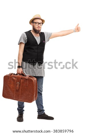 Full length portrait of a young hipster holding a brown suitcase and hitchhiking with his thumb isolated on white background - stock photo