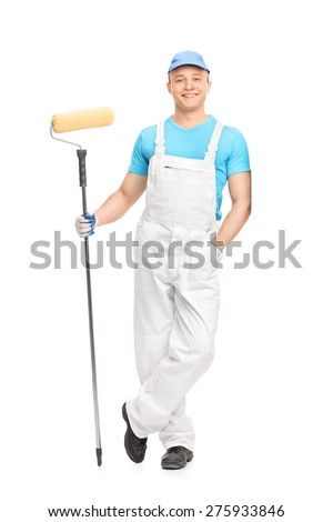 Full length portrait of a young male decorator holding a paint roller and leaning against a wall isolated on white background