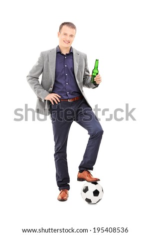Full length portrait of a young male football fan holding a beer and standing with a ball under his foot isolated on white background - stock photo