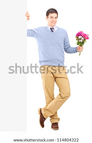 Full length portrait of a young male holding flowers and posing next to a white panel - stock photo