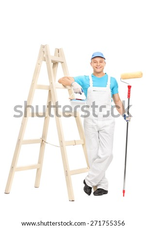 Full length portrait of a young male house painter in a white clean jumpsuit holding a paint roller and leaning on a wooden ladder isolated on white background - stock photo