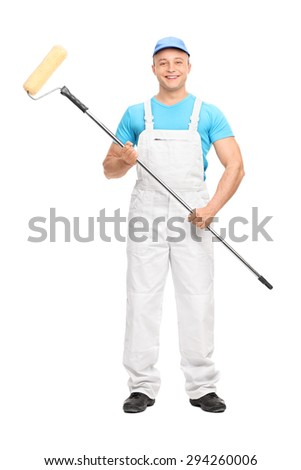 Full length portrait of a young male house painter in a white overalls holding a paint roller and looking at the camera isolated on white background - stock photo
