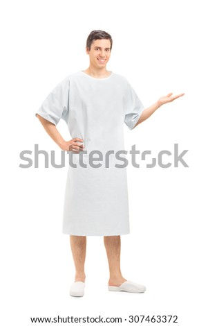 Full length portrait of a young male patient in a hospital gown gesturing with his hand and looking at the camera isolated on white background - stock photo