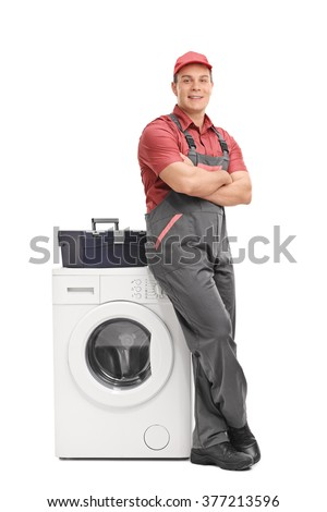 Full length portrait of a young male repairman leaning on a washing machine isolated on white background