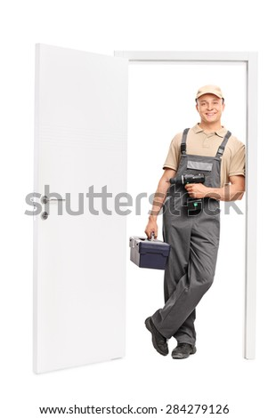 Full length portrait of a young male worker holding a toolbox and a hand drill and leaning against the frame of an open door isolated on white background - stock photo