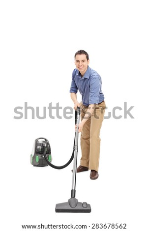 Full length portrait of a young man cleaning with a vacuum cleaner and smiling towards the camera isolated on white background
