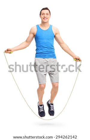 Full length portrait of a young man exercising with a skipping rope and looking at the camera isolated on white background - stock photo