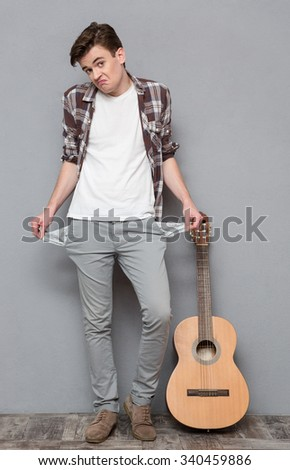 Full length portrait of a young man exhibiting his empty pockets on gray background - stock photo