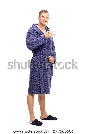 Full length portrait of a young man in blue bathrobe holding a cup of coffee and looking at the camera isolated on white background - stock photo