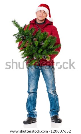 Full length portrait of a young man in winter clothing and Santa hat with artificial fir tree isolated on white background - stock photo