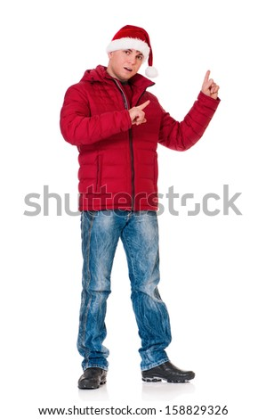 Full length portrait of a young man in winter clothing with Santa hat showing something isolated on white background - stock photo